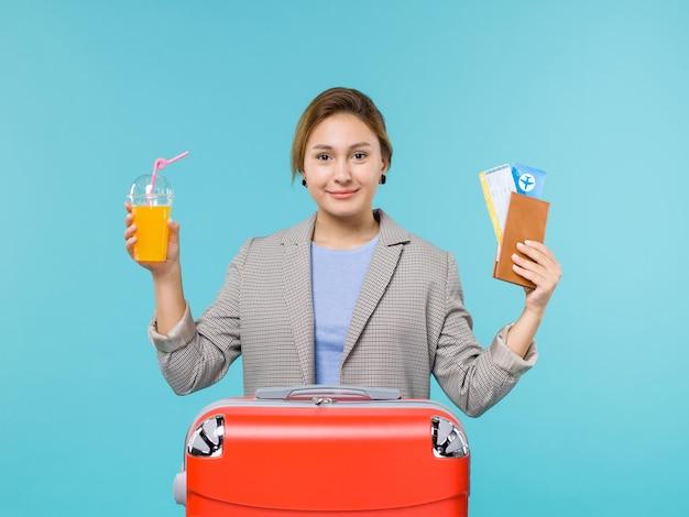 Mulher de frente para as férias segurando suco fresco e ingressos no fundo azul do mar, férias, avião, viagem, viagem, viagem, viagem