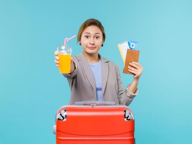 Mulher de frente para as férias segurando suco fresco e ingressos no piso azul mar férias avião viagem viagem viagem