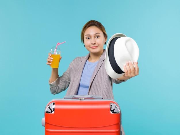 Mulher de frente para as férias segurando suco fresco e o chapéu dela sobre fundo azul claro viagem mar férias viagem viagem