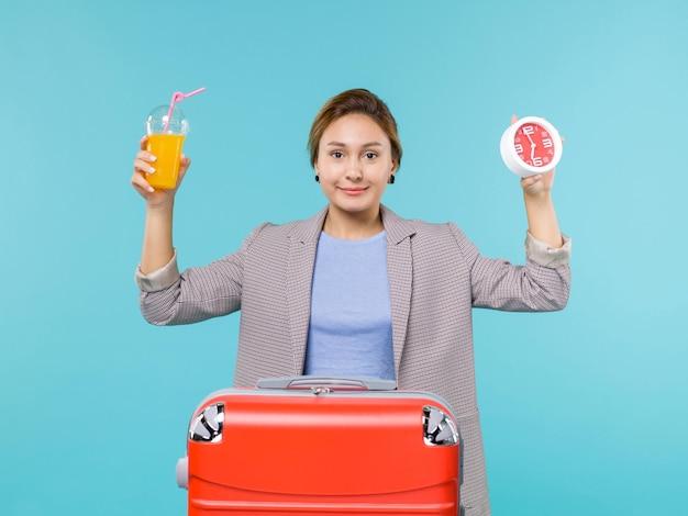 Mulher de frente para as férias segurando suco fresco e relógio no fundo azul viagem viagem de férias viagem marítima
