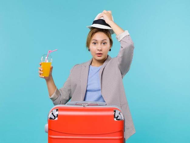 Mulher de frente para as férias segurando suco fresco e seu chapéu na viagem de viagem de viagem de férias de fundo azul do mar