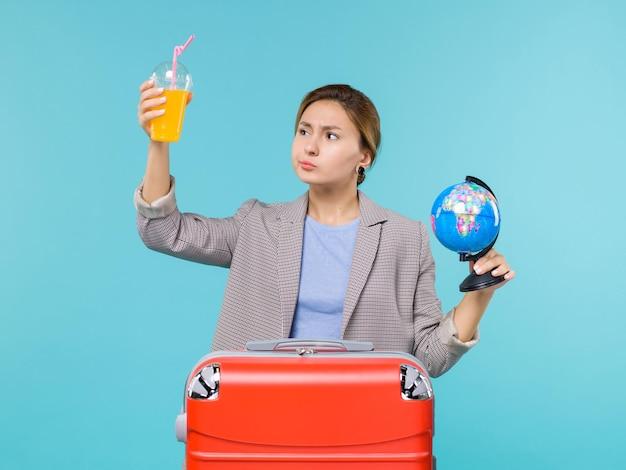 Mulher de frente para as férias segurando suco fresco e um globo em um fundo azul.