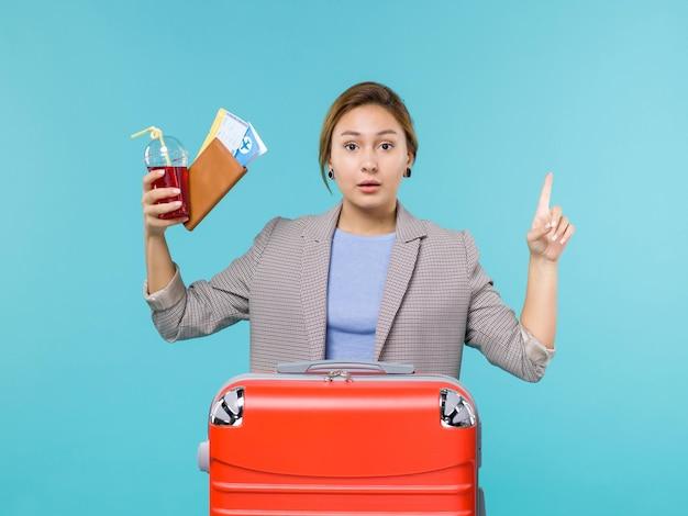 Mulher de frente para as férias segurando um copo de suco fresco e ingressos no fundo azul viagem avião férias viagem viagem mar