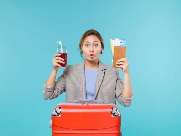 Mulher de frente para as férias segurando um copo de suco fresco e ingressos no fundo azul viagem viagem avião viagem de férias