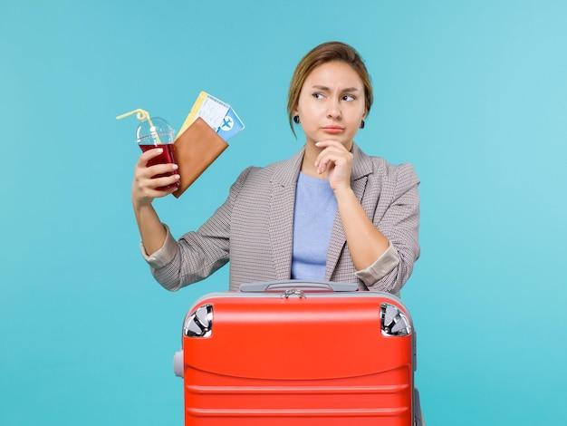 Mulher de frente para as férias segurando um copo de suco fresco e ingressos no piso azul voyage avião férias viagem viagem mar