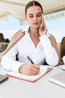 Mulher de frente para escrever no caderno