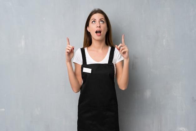 Mulher de funcionário surpreso e apontando para cima
