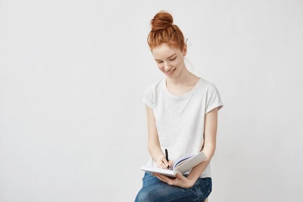 Mulher de gengibre feliz escrevendo no caderno sorrindo.