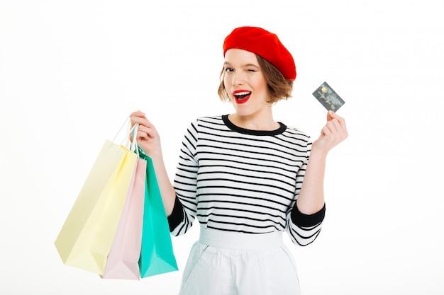 Mulher de gengibre satisfeito com pacotes segurando o cartão de crédito e piscadelas para a câmera sobre cinza