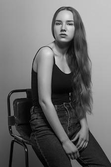 Mulher de gesto sentar na cadeira e olhando para a câmera. foto de estúdio, isolada em fundo cinza
