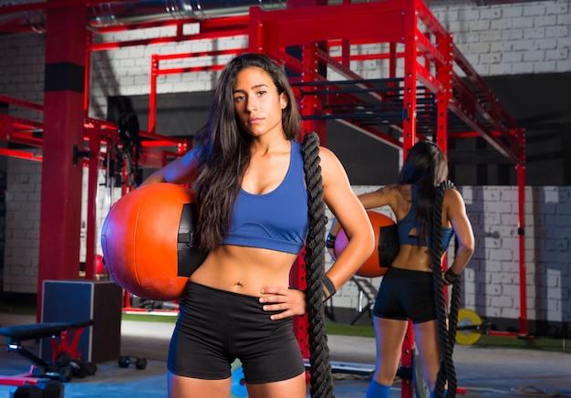 Mulher de ginásio com bola e corda ponderada