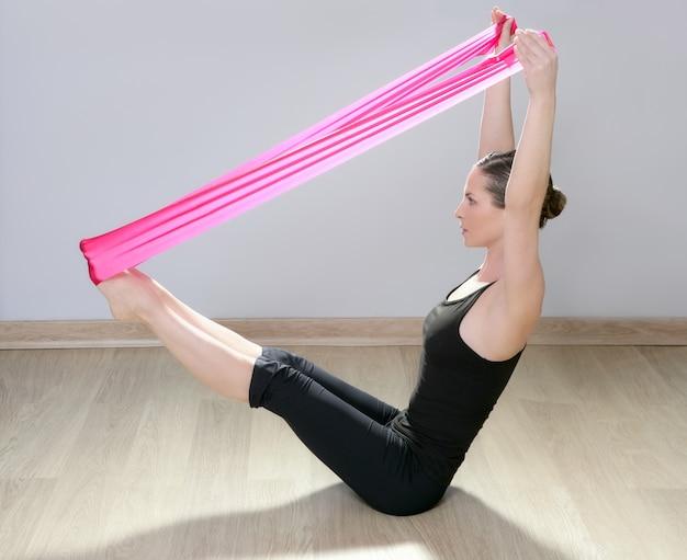 Mulher de ginásio de borracha vermelha de banda de resistência de pilates yoga