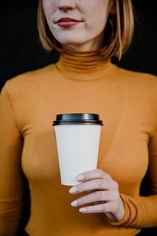 Mulher de gola alta com um copo de papel para viagem