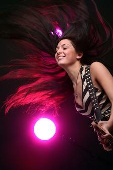 Mulher de heavy metal tocando guitarra elétrica