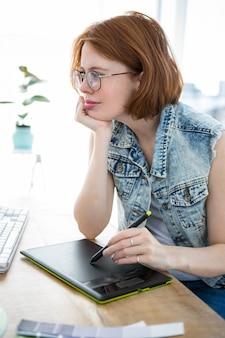 Mulher de hipster na mesa dela, escrevendo em um taablet de desenho digital