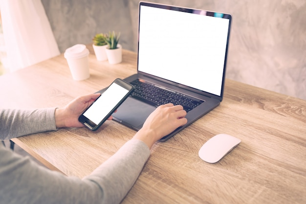 Mulher de hipster, segurando o telefone e usando o laptop na mesa de madeira em cafeteria.