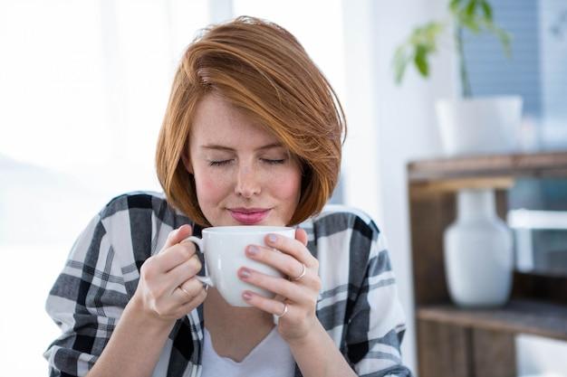 Mulher de hipster sorridente com os olhos fechados, cheirando uma xícara de café