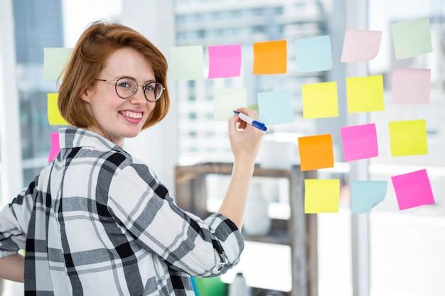 Mulher de hipster sorridente em seu escritório, furando notas para uma parede