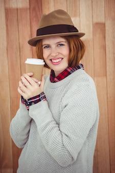 Mulher de hipster sorridente em um chapéu, segurando um café