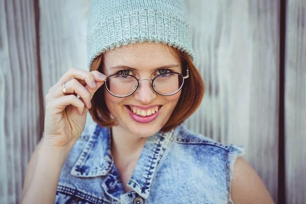 Mulher de hipster sorridente em um gorro e óculos contra um baackkground de madeira