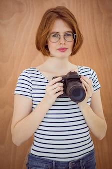 Mulher de hipster sorridente segurando uma câmera digital contra uma madeira