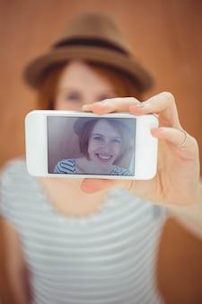Mulher de hipster sorridente tomando uma selfie