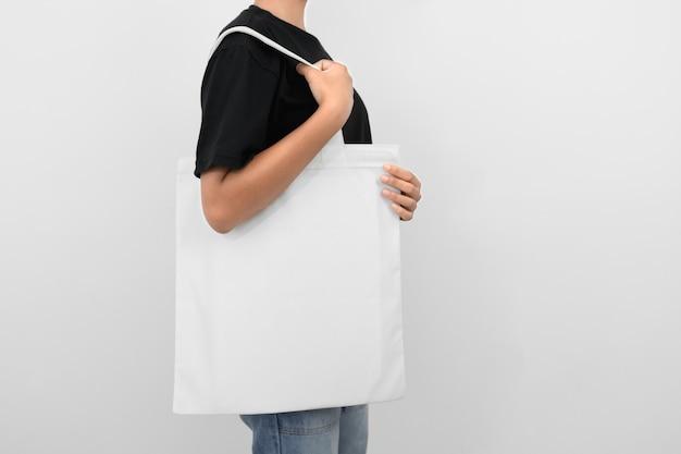 Mulher de hipter segurando o saco de tecido ecológico isolado no branco