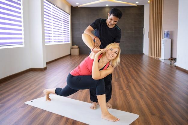 Mulher de instrutor ajudando a fazer pose de ângulo lateral revolvido