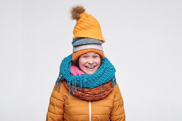 Mulher de inverno bonito brincalhão em lenços e chapéu rindo
