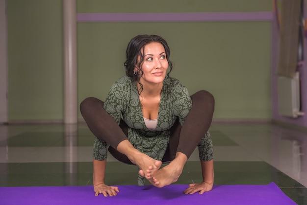 Mulher de ioga alongamento em ioga no ginásio. / garota de ioga realizando poses de ioga.