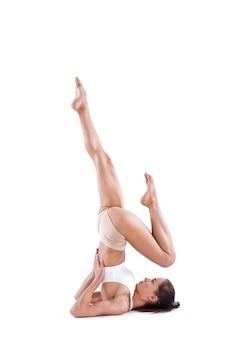 Mulher de ioga com corpo perfeito em equilíbrio de comprimento total isolado no branco. menina apta.