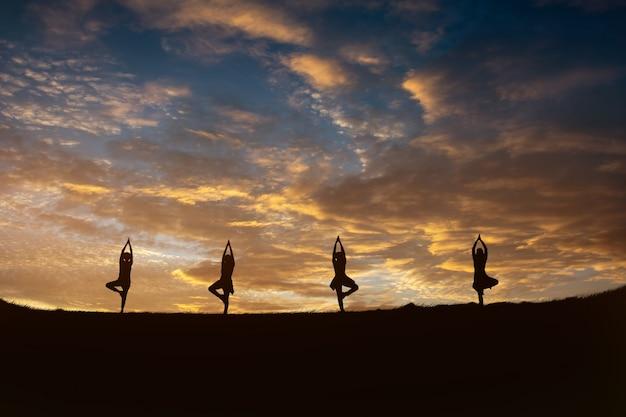 Mulher de ioga jovem aptidão meditando no pico da montanha ao nascer do sol