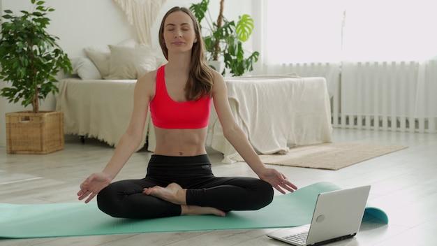 Mulher de ioga positiva pratica na frente de um laptop enquanto está sentada em uma esteira esportiva em casa