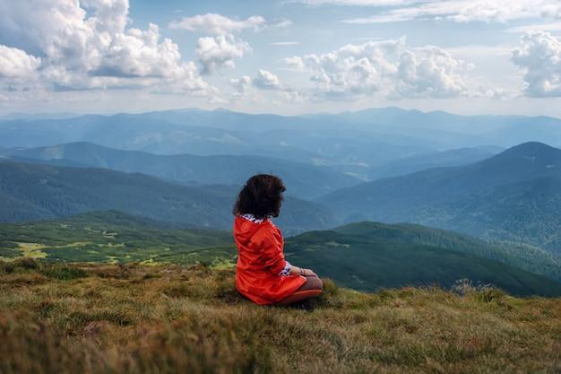 Mulher de ioga sente-se em pose de lótus no pico da montanha. turista de mulher pratica ioga e medita na montanha. descansando na colina mais alta.