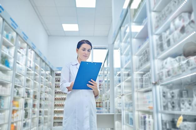 Mulher de jaleco branco com pasta na farmácia