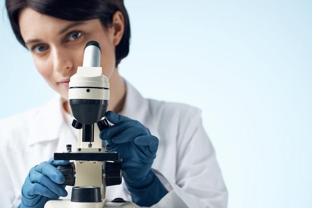 Mulher de jaleco branco, profissionais de diagnóstico de pesquisa de microscópio