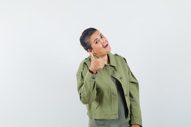 Mulher de jaqueta, camiseta mostrando o polegar e parecendo confiante