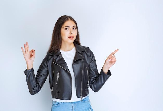 Mulher de jaqueta de couro, mostrando algo à direita.