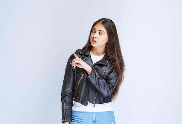 Mulher de jaqueta de couro, mostrando algo abaixo.