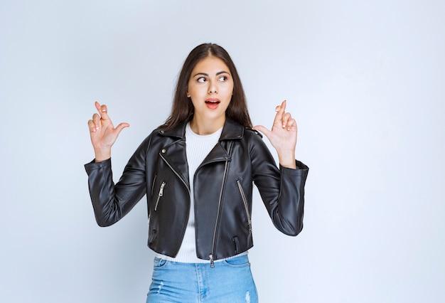 Mulher de jaqueta de couro, mostrando o dedo cruzado.