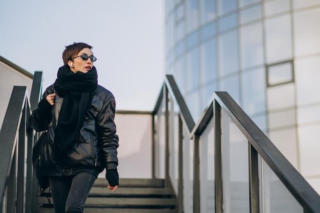 Mulher de jaqueta preta andando pela ponte