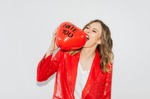 Mulher de jaqueta vermelha mordendo um balão vermelho com o texto eu odeio você