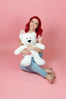 Mulher de jeans com cabelo vermelho abraçando um grande urso de pelúcia branco sentado no chão