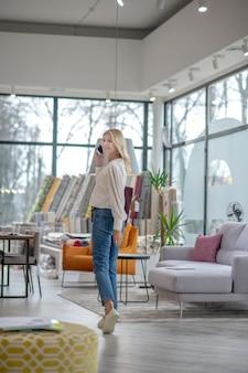 Mulher de jeans e mocassins brancos, segurando um smartphone perto da orelha, de pé em um salão de móveis espaçosos, de bom humor.