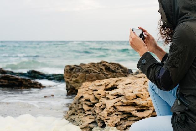 Mulher de jeans e uma jaqueta verde com um capuz fotos do mar ao telefone no outono