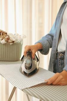 Mulher de jeans passando toalha de cozinha na tábua de passar