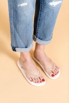Mulher de jeans rasgado em pé sobre um fundo bege