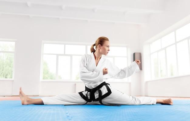 Mulher de karatê, vestindo quimono, esticando a perna antes de treino duro.