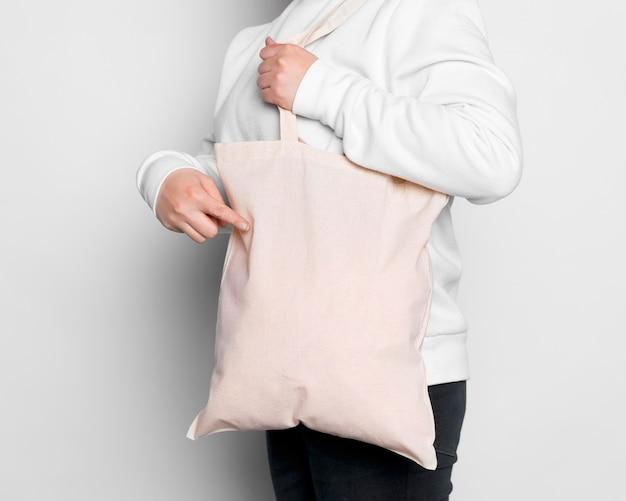 Mulher de lado carregando sacola de tecido