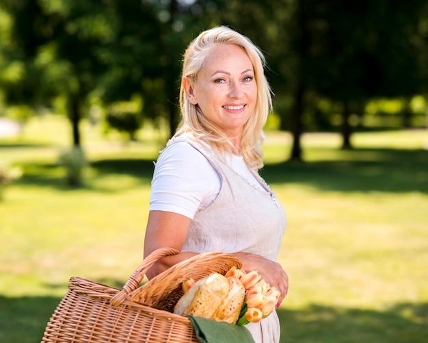 Mulher de lado com uma cesta olhando para a câmera